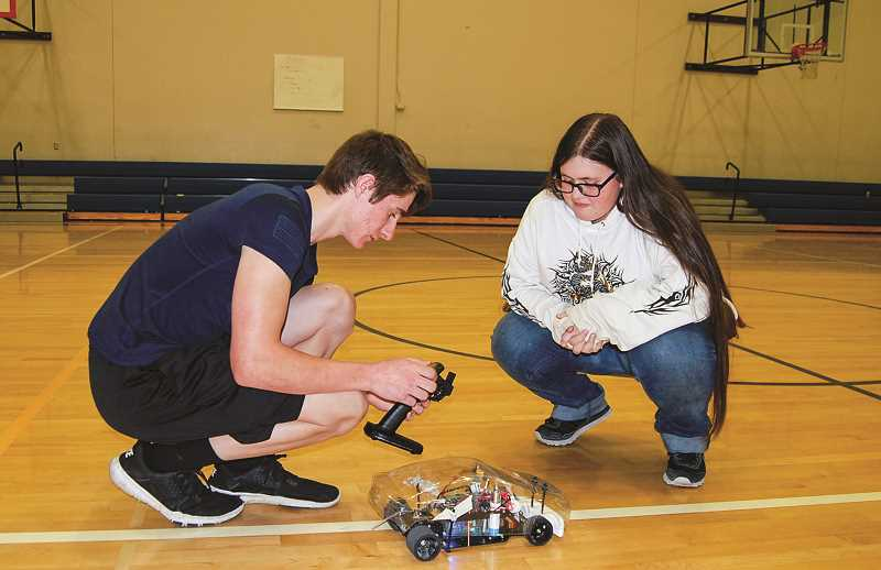 RAMONA MCCALLISTER - From left to right: Senior Hank Heiges and Senior Kelci Hale do some work on the remote control before their test run on Tuesday.