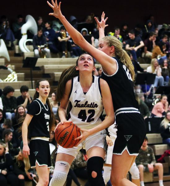 PMG PHOTO: DAN BROOD - Tualatin High School senior post Natalie Lathrop (42) looks to go up to the basket against Tigard sophomore Sarah Lamet during Wednesday's Three Rivers League game.