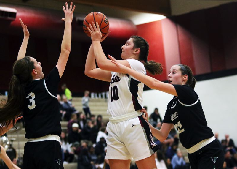 PMG PHOTO: DAN BROOD - Tualatin High School junior Kasidy Javernick (10) shoots between Tigard's Karen Spadafora (left) and Delaney Leavit during the Wolves' 48-38 victory in Three Rivers League play.