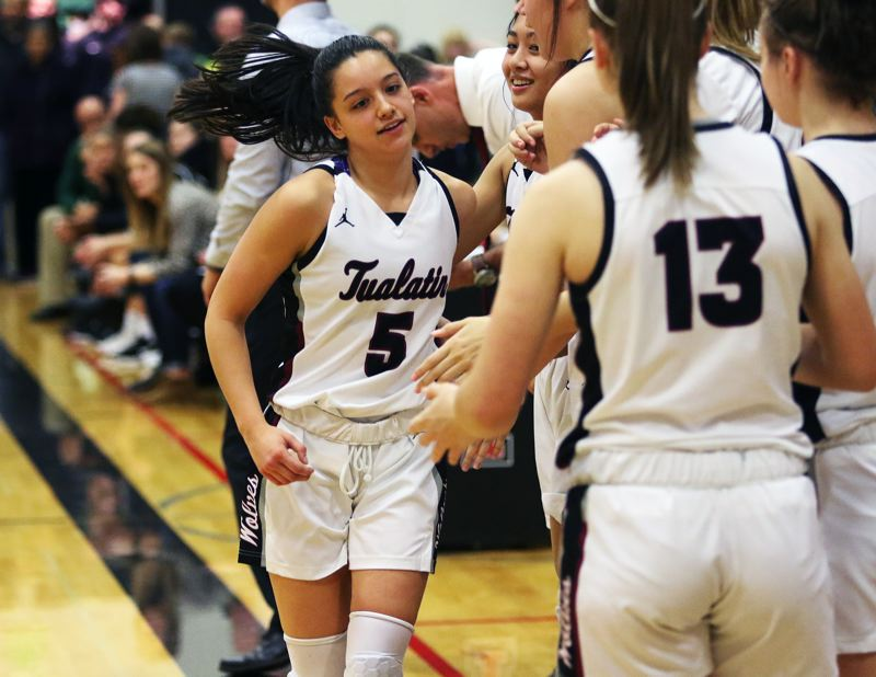 PMG PHOTO: DAN BROOD - Tualatin High School senior Sophie Bennett (5) is congratulated by her Timberwolf teammates as she comes to the bench late in the game during Tualatin's 48-38 win over Tigard.
