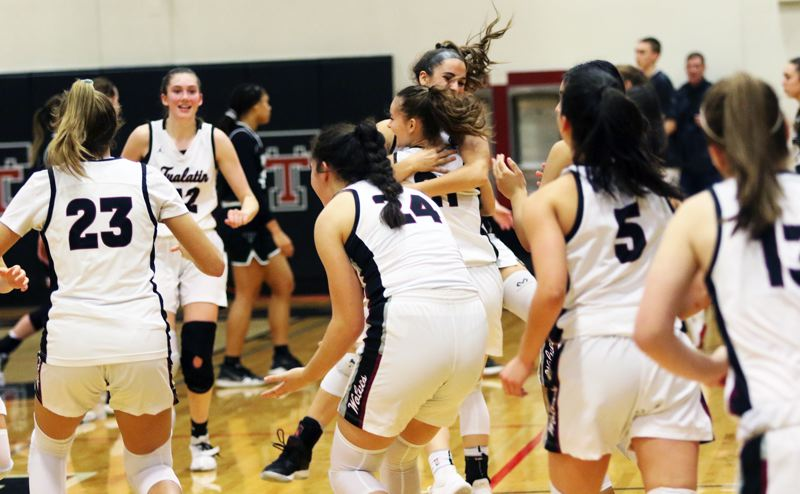 PMG PHOTO: DAN BROOD - Members of the Tualatin High School girls basketball team start to celebrate following the Wolves' 48-38 victory over rival Tigard.
