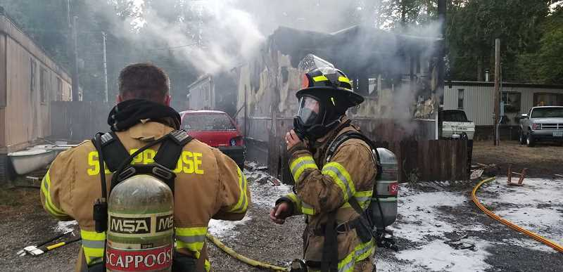 PMG FILE PHOTO - Scappoose firefighters on the scene of a trailer fire. Under a proposal to establish a fire authority, a separate district formed for the purpose of managing personnel, Scappoose and Columbia River Fire and Rescue firefighters would begin operating under the fire authority framework in July 2021.