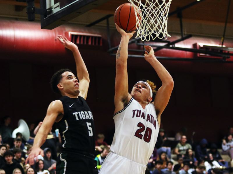 PMG PHOTO: DAN BROOD - Tualatin High School senior John Miller (20), with Tigard junior Drew Carter to his right, goes up to the basket during the Wolves' 70-66 come-from-behind victory.