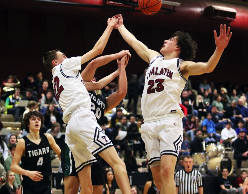 PMG PHOTO: DAN BROOD - Tualatin High School junior Carson Denning (left) and sophomore Peter Burke go for a loose ball during the Timberwolves' 70-66 league win over Tigard.