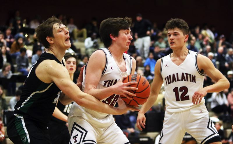 PMG PHOTO: DAN BROOD - Tualatin High School senior Bret Robert (center), with teammate Sam Noland to his left, grabs the ball in front of Tigard senior Dylan Berg during the teams' Three Rivers League game.