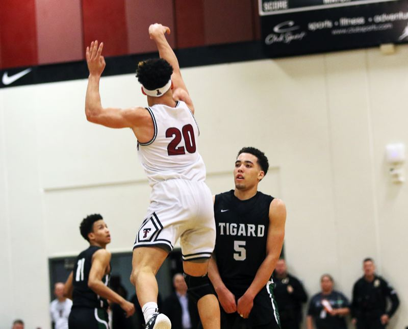 PMG PHOTO: DAN BROOD - Tualatin High School senior John Miller (20) shoots a half-court shot as time runs out in the second quarter. Miller banked in the shot.