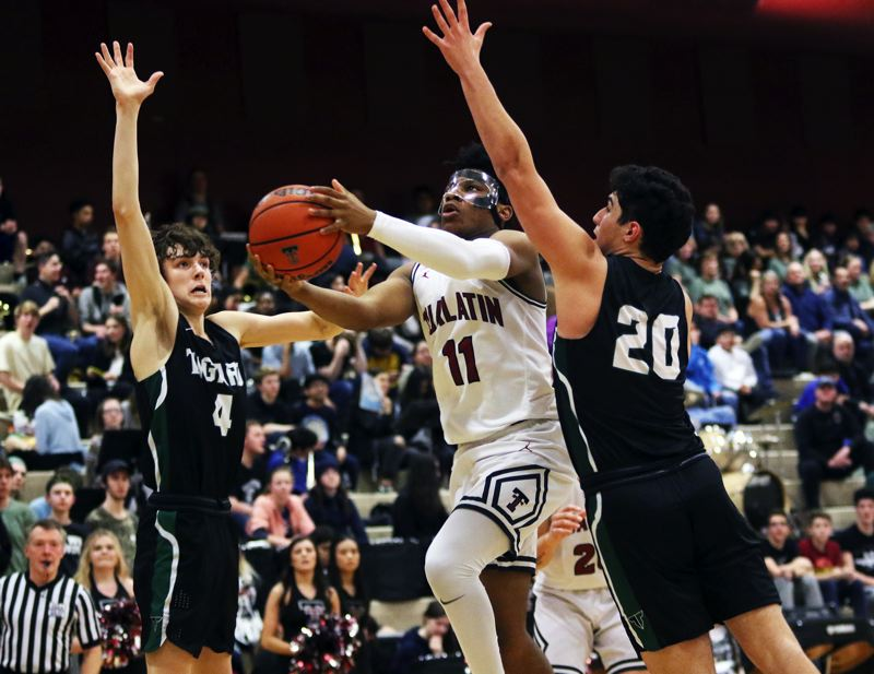 PMG PHOTO: DAN BROOD - Tualatin High School sophomore Malik Ross (11) tries to get to the basket between Tigard's Brett Moss (4) and Edward Beglaryan during the teams' Three Rivers League game.