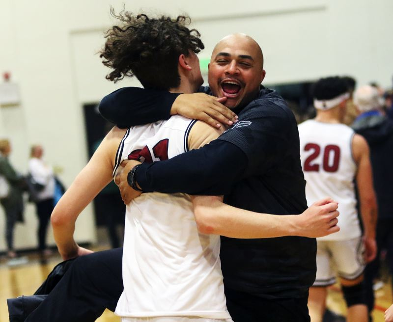 PMG PHOTO: DAN BROOD - Tualatin High School junior Logan Shaw (left) gets a hug from Timberwolves' assistant coach Bubba Lemon following the team's 70-66 win over rival Tigard.