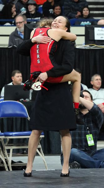 PMG PHOTO - Emma Baertlein leaps into the arms of Oregon City coach Na'Tasha Umemoto after clinch the first girls state title in program history Saturday.