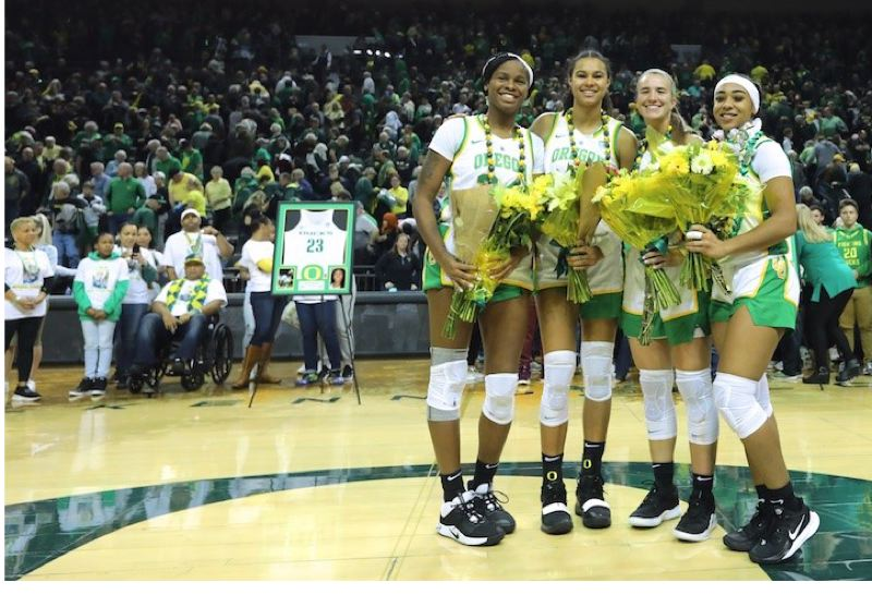 PMG PHOTO: JAIME VALDEZ - Oregon fans salute (from left) senior Ruthy Hebard, WNBA-bound junior Satou Sabally, senior Sabrina Ionescu and senior Minyon Moore after their final regular-season home game at Matthew Knight Arena. The Ducks topped Washington 92-56.