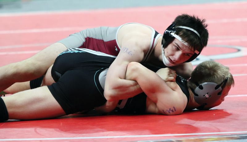 PMG PHOTO: DAN BROOD - Tualatin High School junior Josiah Ingham (top) is in control in his 132-pound match with Century's William Musser on Saturday at the Class 6A state wrestling tournament.