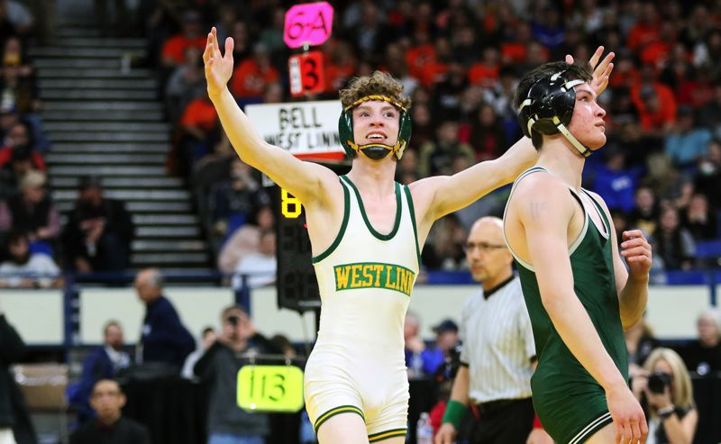 PMG PHOTO: DAN BROOD - West Linn junior Ricky Bell raises his arms in triumph after winning the Class 6A state title at 113 pounds on Saturday, Feb. 29, at Veterans Memorial Coliseum.