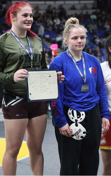 STEELE HAUGEN - Senior Bailey Dennis, right, a three-time state champion, stands on the second-place podium at the tournament.