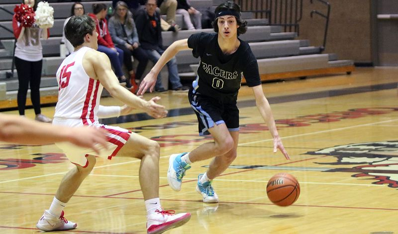 PMG PHOTO: JIM BESEDA - Lakeridge senior Carson Mike initiates the Pacers' offense under pressure from Oregon City's Dalton Welch during Lakeridge's 72-36 loss at Oregon City High School on Wednesday, Feb. 26.