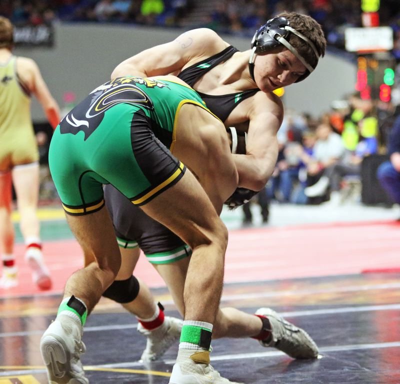 PMG PHOTO: DAN BROOD - Tigard High School senior Cameron O'Connor (right) tries to take down Cleveland's Elija Fishler in a 113-pound semifinal match at the Class 6A state tournament. O'Connor won 4-2 in overtime.