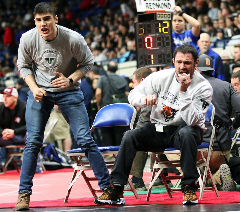 PMG PHOTO: DAN BROOD - Tigard High School assistant wrestling coach Joey Stefani (left) and head coach Geoff Jarman watch the action when Tiger senior Cameron O'Connor took on Cleveland's Elija Fishler in a Class 6A state tournament semifinal match.