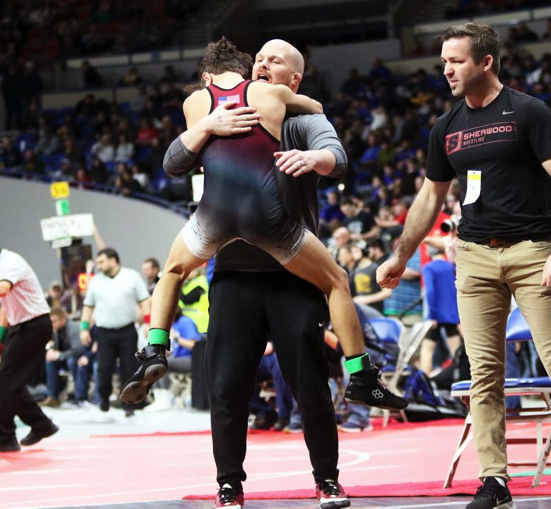 PMG PHOTO: DAN BROOD - Sherwood High School sophomore Ethan Ritchie celebrates with Bowmen head coach Jeff Wilson following his 106-pound semifinal victory at the Class 6A state wrestling tournament.