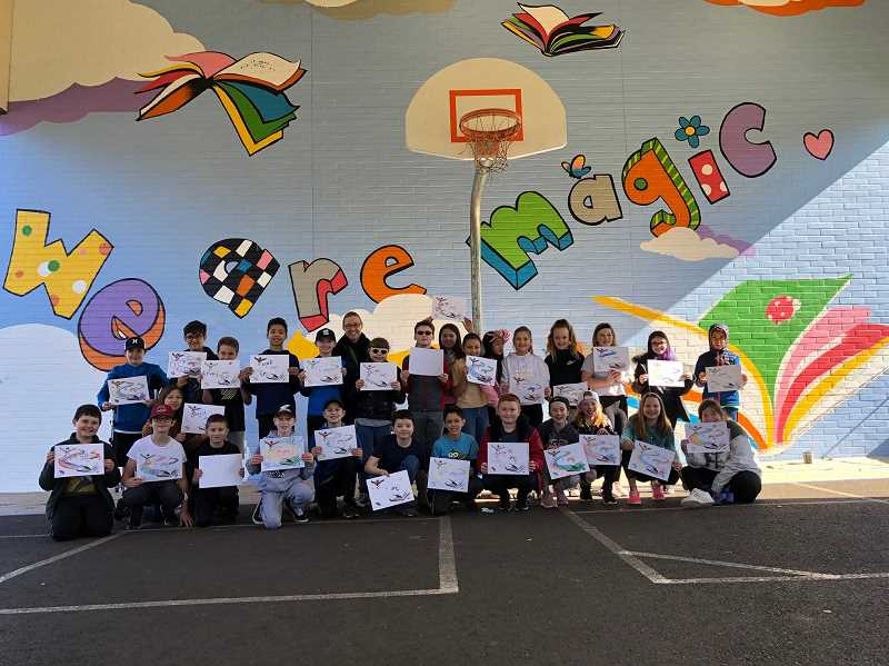 Kelly Fennells fifth grade class proudly shows off its own artistic creations last week.