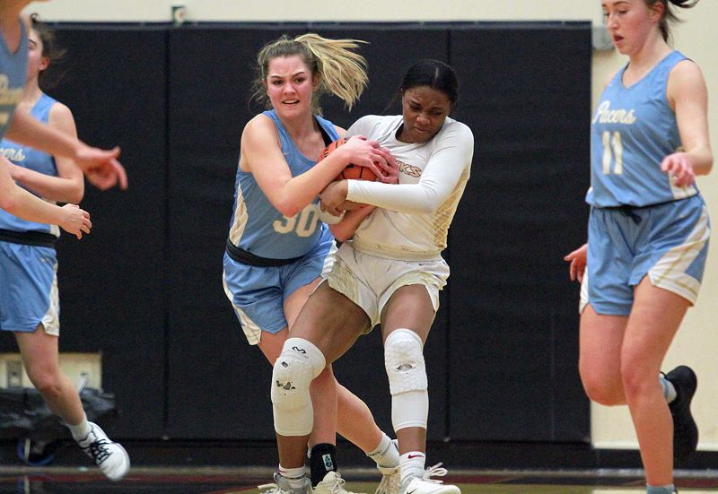 PMG PHOTO: MILES VANCE - Lakeridge junior Addie Reardon (left) battles Southridge's Emoney Perry-Reid for possession of the ball during the Pacers' 65-47 loss at Southridge High School in the first round of the Class 6A state playoffs on Tuesday, March 3.