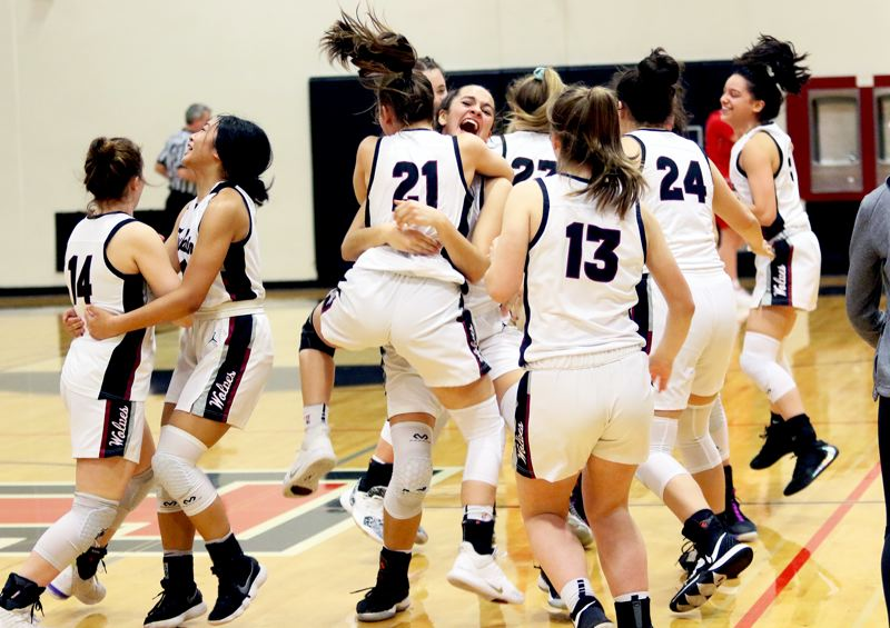 PMG PHOTO: DAN BROOD - Members of the Tualatin High School girls basketball team start celebrating following their 50-40 double-overtime win over Clackamas in Tuesday's Class 6A state playoff game.