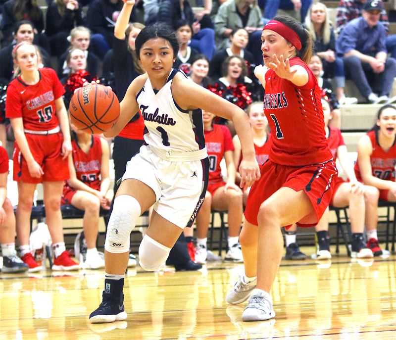 PMG PHOTO: DAN BROOD - Tualatin High School junior guard Teagan Gaviola (left) drives the baseline against Clackamas sophomore Ava Peterson during Tuesday's Class 6A state playoff game.