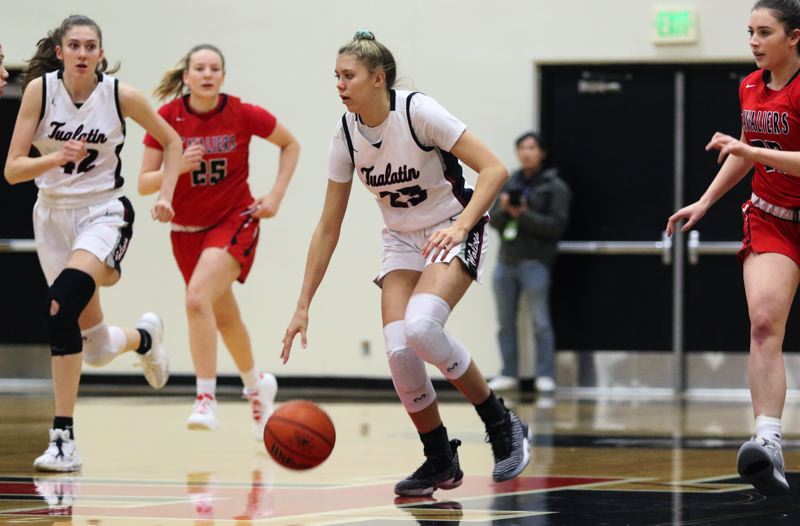 PMG PHOTO: DAN BROOD - Tualatin High School freshman guard Tabi Searle (23) brings the ball up court on a fast break during the Wolves' 50-40 double-overtime win over Clackamas on Tuesday.