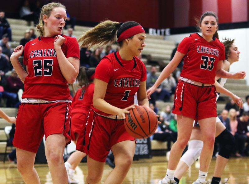PMG PHOTO: DAN BROOD - Clackamas sophomore guard Ava Peterson (1), between teammates Sydney Benedict (25) and Maddie Tacheny, looks to get the ball up court after grabbing a rebound during Tuesday's Class 6A state playoff game at Tualatin.