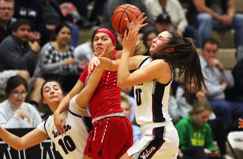 PMG PHOTO: DAN BROOD - From left, Tualatin's Kasidy Javernick, Clackamas' Ava Peterson and Tualatin's Aurora Davis battle over a loose ball during the Timberwolves' 50-40 double-overtime in in Tuesday's Class 6A state playoff game.