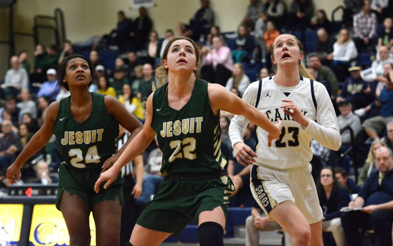 PMG MEDIA PHOTO: DEREK WILEY -  Jesuits Kendall Kirkland, No. 24, and Taylor Freeman, No. 22, box out Canby senior Nicole Mickelson.