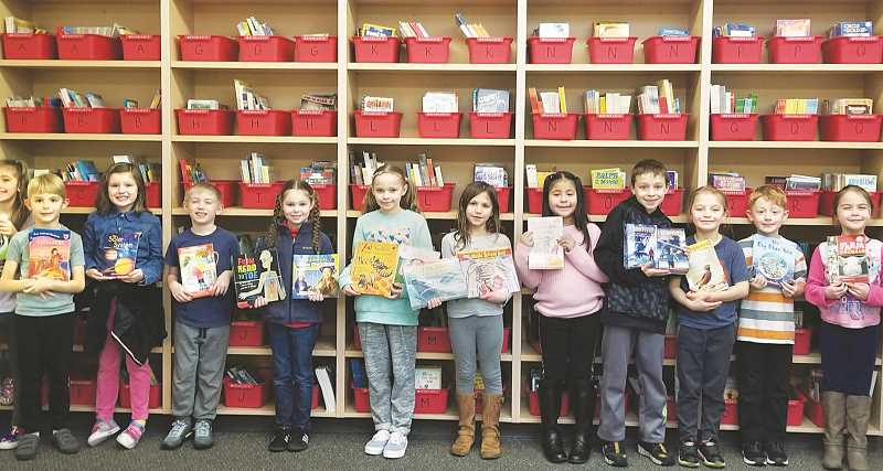 SUBMITTED PHOTO - A group of Joan Austin Elementary School students show off the new books and improve accomodations in the school's renovated book room.