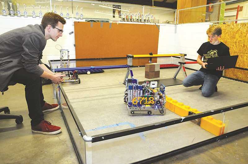 GRAPHIC PHOTO: GARY ALLEN - Seniors Colee Hufschmid (left) and Paul Sperling do 'path testing' in anticipation of the NHS robotics team's next competition.