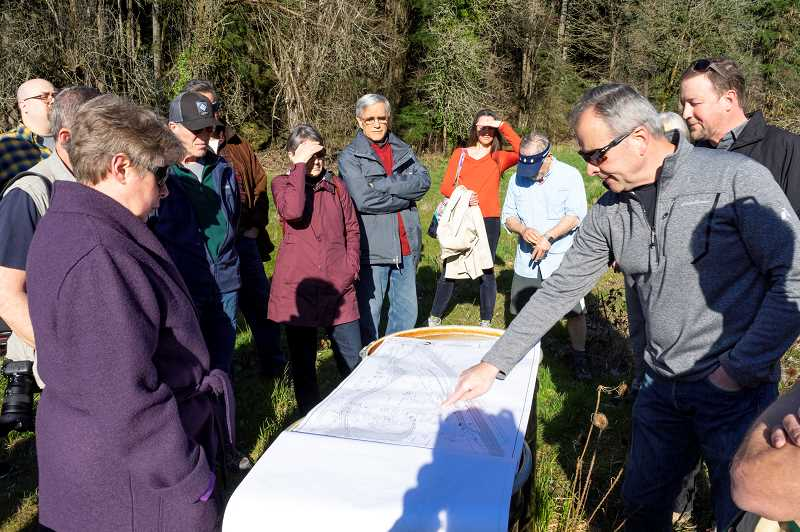 PMG PHOTO: CLARA HOWELL  - Bruce Powers with the parks department helps explain the construction documents of the proposed park plans to community members.