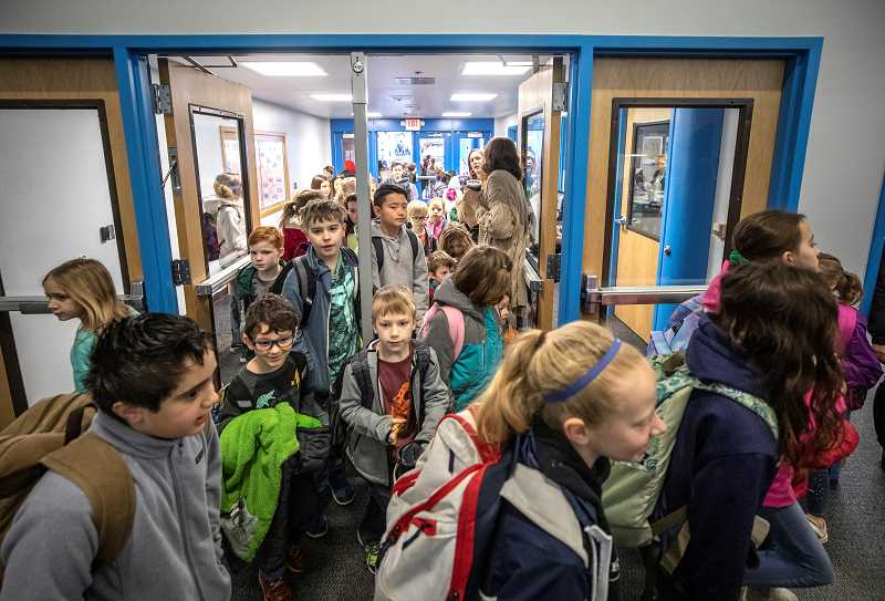 PMG PHOTO: JONATHAN HOUSE - It was business as usual at all Lake Oswego schools, save for Forest Hills Elementary, this week. Here, Hallinan Elementary students rush into school on Wednesday morning.