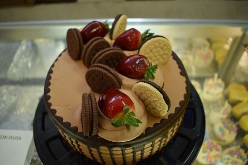 PMG PHOTO: SHANNON O. WELLS - The Neapolitan Cake at Tany's Bakery has the three flavors — chocolate, vanilla and strawberry — of Neapolitan ice cream beneath its chocolate, caramel, cookies and fruit exterior.