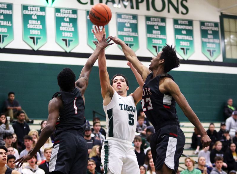 PMG PHOTO: DAN BROOD - Tigard High School junior Drew Carter (5) shoots over David Douglas' Jermaine Robinson (left) and Nassir Pedraza during the teams' state playoff game. Carter scored 34 points in the Tigers' 69-62 win.