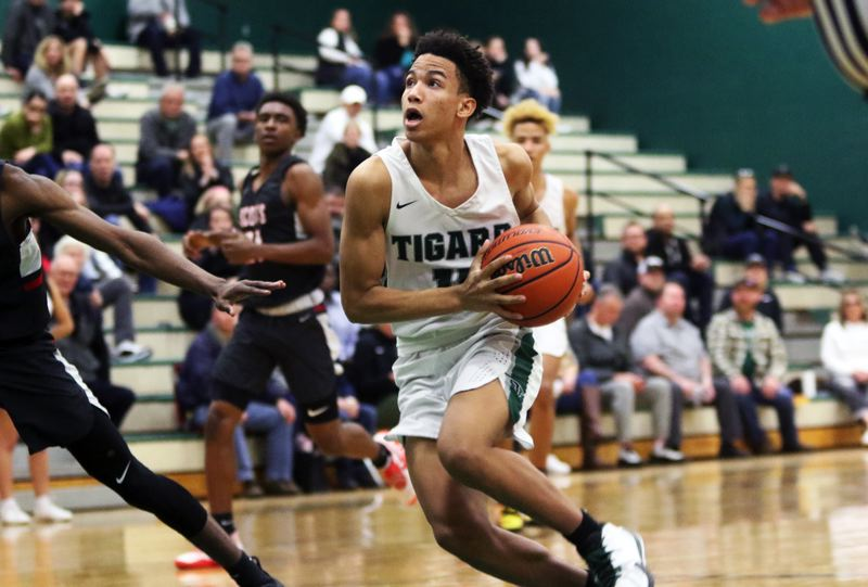 PMG PHOTO: DAN BROOD - Tigard High School freshman guard Kalim Brown looks to drive to the basket during the Tigers' 69-62 state playoff victory over David Douglas.