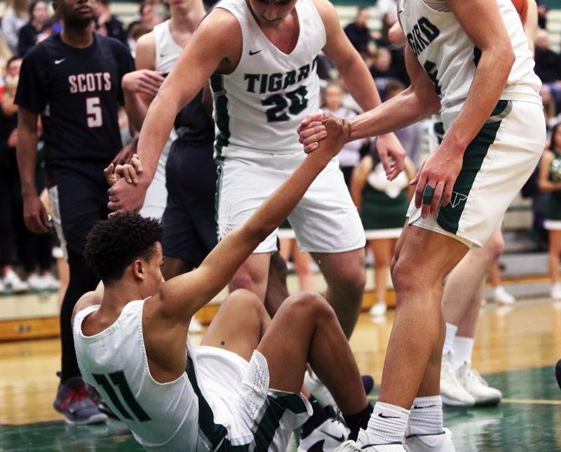 PMG PHOTO: DAN BROOD - Tigard High School freshman Kalim Brown is helped up by his Tiger teammates after drawing a charge during the Tigers' 69-62 state playoff victory over David Douglas.