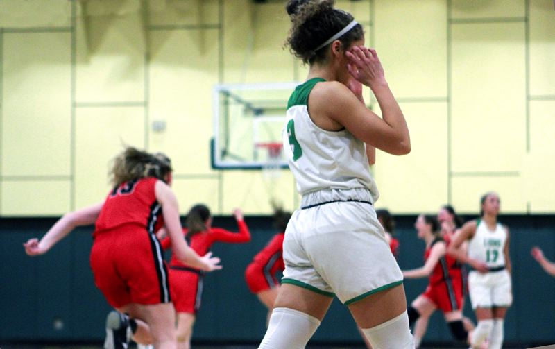 PMG PHOTO: MILES VANCE - West Linn sophomore Alana Molden walks off the court as McMinnville's players celebrate at the end of their 57-53 upset of the No. 3 Lions at West Linn High School on Friday, March 6.