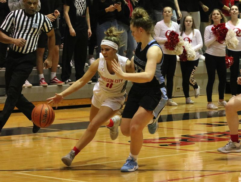 PMG PHOTO: JIM BESEDA - Oregon City's Tyra Bradford (11) runs into defensive resistance from Mountainside's Carly Stone during the fourth quarter for Friday's OSAA 6A girls basketball playoff game at Oregon City.