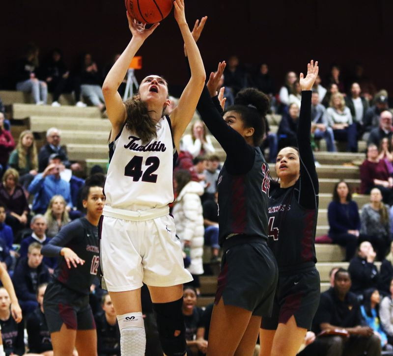 PMG PHOTO: DAN BROOD - Tualatin High School junior post Natalie Lathrop (42) looks to go up to the basket during the Timberwolves' Class 6A state playoff game with Southridge. Lathrop led Tualatin with 13 points.