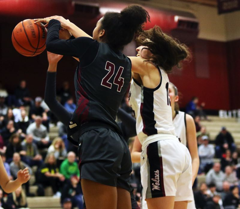 PMG PHOTO: DAN BROOD - Southridge High School junior Kilyn Dawkins (24) battles for the ball during Friday's state playoff game at Tualatin. Dawkins had nine rebounds in the Skyhawks' 51-48 victory.