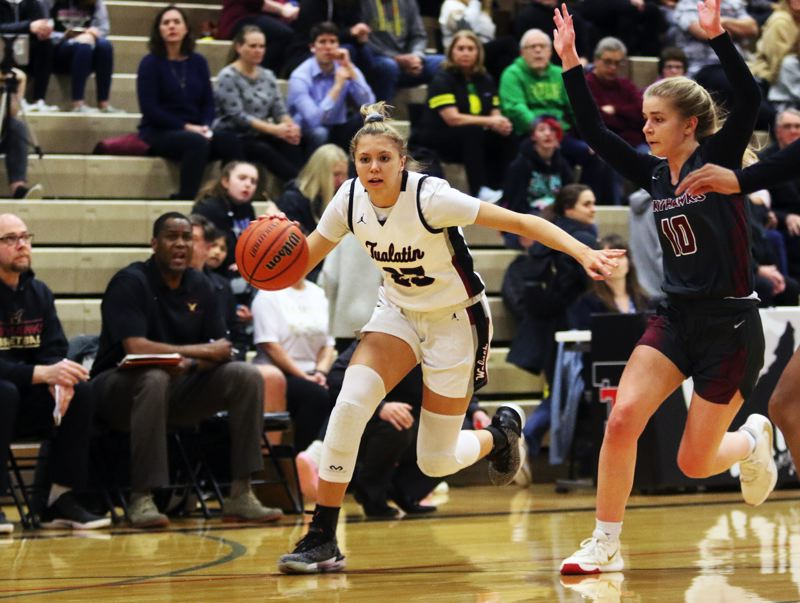 PMG PHOTO: DAN BROOD - Tualatin High School freshman Tabi Searle (left) looks to drive with the ball after coming up with a steal during the Timberwolves' state playoff game with Southridge on Friday.