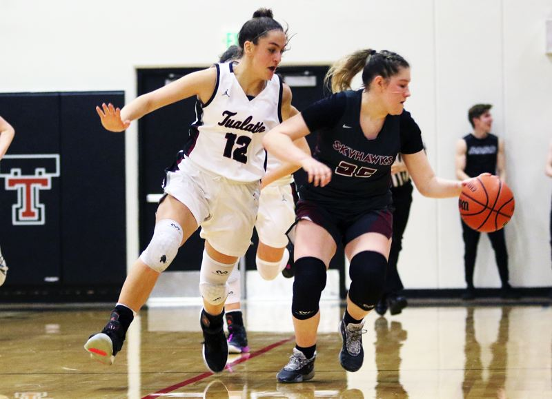 PMG PHOTO: DAN BROOD - Southridge High School senior Kaylen Blair (right) keeps control of the ball against Tualatin junior Sidney Dering during Friday's Class 6A state playoff game.