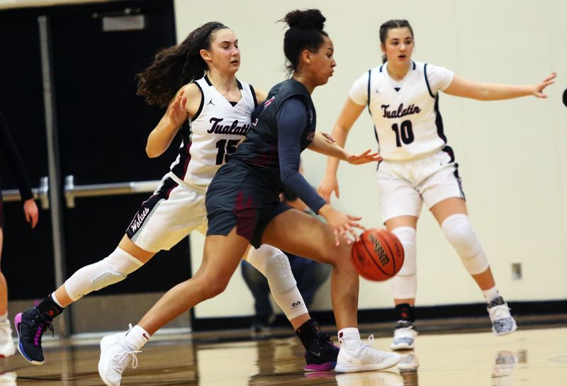 PMG PHOTO: DAN BROOD - Southridge High School junior Maya Hoff looks to drive against Tualatin junior Aurora Davis during Friday's Class 6A state playoff game. Hoff had six assists in the Skyhawks' 51-38 victory.