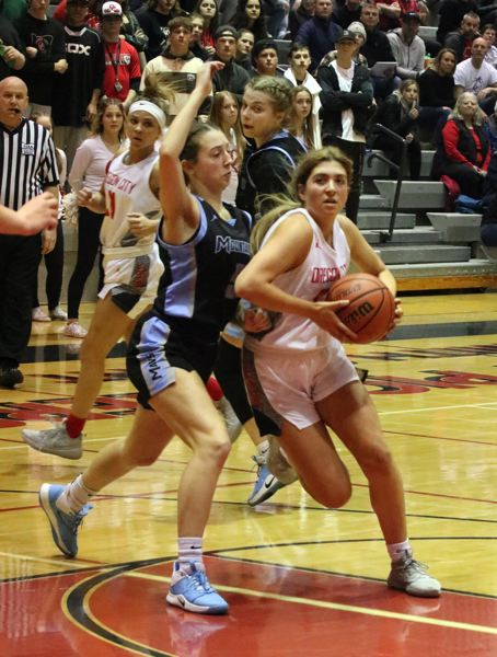 PMG PHOTO: JIM BESEDA - Oregon City's Katie Kathan drives on Mountainside's Abby Crawshaw in the second half of Friday's OSAA 6A girls basketball playoff game.
