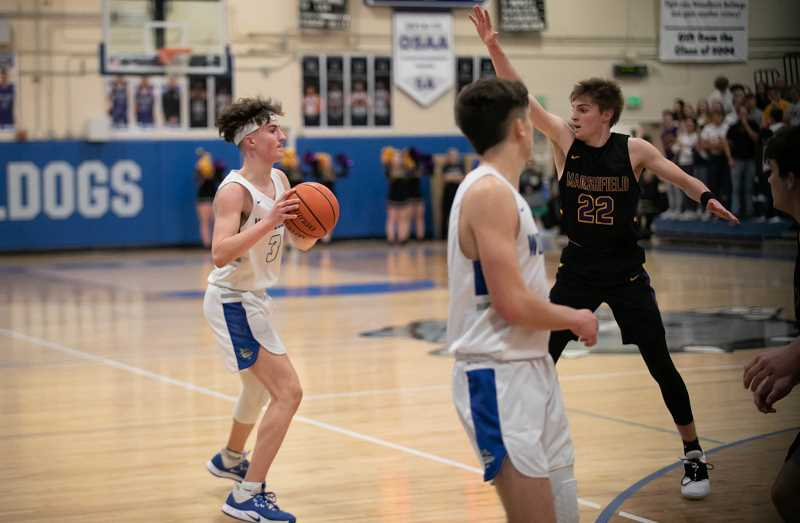 COURTESY PHOTO: RICK VASQUEZ - Woodburn senior Carter Nelson hit a clutch corner 3-point shot in overtime to help give the Bulldogs the cushion needed to outlast the visiting Marshfield Pirates in the first round of the state playoffs.