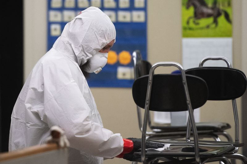 PMG PHOTO: CHRISTOPHER OERTELL - Wearing protective equipment, workers sanitize classroom equipment and furniture Sunday evening, March 8, at South Meadows Middle School in Hillsboro.