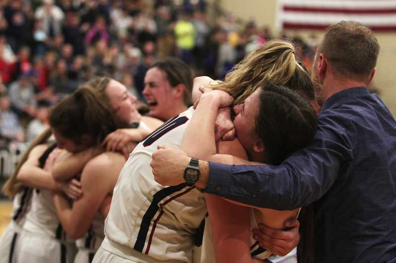 PMG PHOTO: PHIL HAWKINS - Kennedy's Sophia Carley and Hailey Arritola embrace next to co-head coach Peter Hall as the rest of the team celebrates behind them in the moments following the Trojans' 48-26 victory over the Monroe Dragons in the 2020 2A Girls Basketball State Championship Saturday in Pendelton.