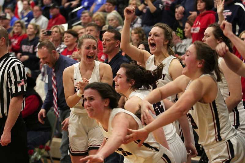 PMG PHOTO: PHIL HAWKINS - The Kennedy girls basketball team erupts onto the court at the Pendleton Convention Center on Saturday to celebrate the Trojans' 48-26 win over Monroe in the 2020 2A Girls Basketball State Championship game.