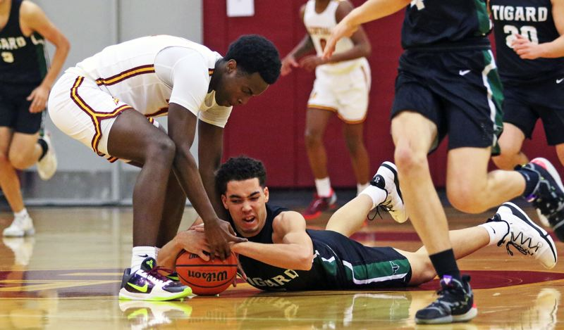 PMG PHOTO: DAN BROOD - Tigard High School junior Drew Carter (right) battles Central Catholic junior Darius Gakwasi for a loose ball during Saturday's Class 6A second-round state playoff game.